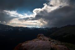 Drastische Wolken über Schnee mit einer Kappe bedeckten Bergen Stockfotografie