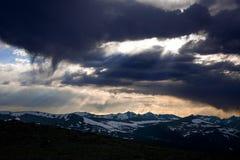 Drastische Wolken über Schnee mit einer Kappe bedeckten Bergen Stockbilder