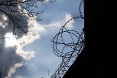 Drastische Wolken hinter Stacheldrahtzaun auf Gefängnismauer Lizenzfreie Stockfotos