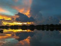 Drastischer Beitragsturm, Licht und dunkler Sonnenuntergang, die über ruhigem See von Bäumen gesäumt in Florida sich reflektieren stockfotografie