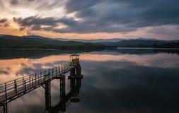 Drastischer bewölkter Sonnenuntergang durch einen See Stockfoto