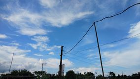 Drastischer blauer Himmel mit elektrischem Draht und Beitrag Stockbild