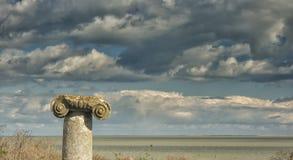 Drastischer blauer Himmel mit weißen Wolken über den Ruinen einer altgriechischen Spalte bei Histria, auf den Ufern von Schwarzem Lizenzfreie Stockbilder