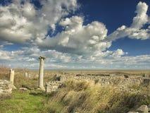 Drastischer blauer Himmel mit weißen Wolken über den Ruinen einer altgriechischen Spalte bei Histria, auf den Ufern von Schwarzem Stockfotos