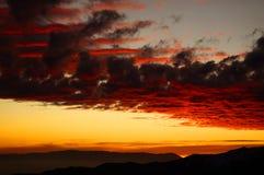 Drastischer brennender Sonnenuntergang über den Bergen Stockfotos