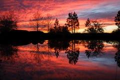 Drastischer brennender Sonnenuntergang mit Reflexionen im Wasser Stockfotos