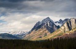 Drastischer Cloudscape-Himmel und entfernter Spitzen-Kanadier Rocky Mountains des schneebedeckten Bergs stockfotografie