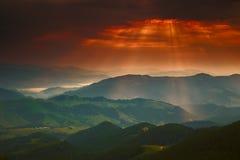 Drastischer goldener Sonnenunterganghimmel mit Sonne und Berg Stockfotos