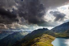 Drastischer Himmel über alpinem See in den Bergen lizenzfreies stockfoto