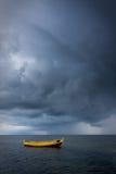 Drastischer Himmel über Boot im Meer Stockbild