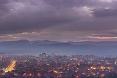 Drastischer Himmel der blauen Stunde über nebelhaftem Stadtbild Stockbild