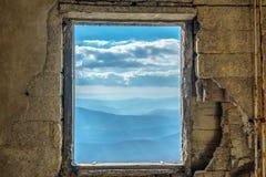Drastischer Himmel des szenischen Bergblicks des Fensters lizenzfreie stockbilder