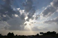 Drastischer Himmel mit den Sonnenlichtstrahlen, die aus Wolken herauskommen Stockbild