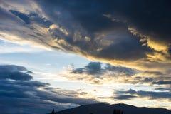 Drastischer Himmel mit dunklen Wolken über dem Berg bei Sonnenuntergang Stockfoto