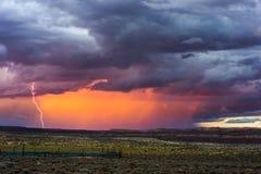 Drastischer Himmel mit Sonnenuntergang und Blitz Stockbilder