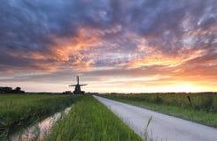 Drastischer purpurroter Sonnenuntergang in der niederländischen Landschaft mit Windmühle lizenzfreie stockfotos