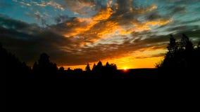 Drastischer roter Sonnenuntergang/Sonnenaufgang mit Federwolkewolken über ländlichem Feld mit Schattenbildern von Bäumen des Wald Lizenzfreie Stockfotografie