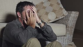 Drastischer Schuss des attraktiven traurigen und deprimierten Mannes, der auf dem glaubenden Wohnzimmerboden hoffnungslose und be