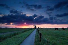 Drastischer Sommersonnenaufgang über niederländischem Ackerland mit Windmühle Lizenzfreie Stockbilder