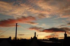 Drastischer Sonnenaufgang über Dachspitzen Stockbilder