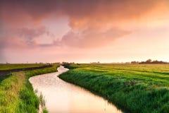 Drastischer Sonnenaufgang über Kanal im Ackerland Lizenzfreie Stockbilder