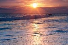 Drastischer Sonnenaufgang über Ozeanbrandung Stockfotos