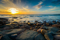 Drastischer Sonnenuntergang auf dem felsigen Strand Stockfotografie