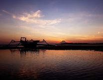 Drastischer Sonnenuntergang an einem Strand mit einem Katamaran und einem Berg Agung lizenzfreie stockfotos