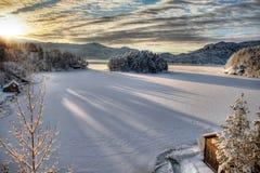 Drastischer Sonnenuntergang in schneebedecktem Norwegen Stockbild