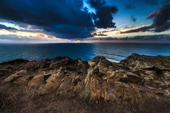 Drastischer Sonnenuntergang strahlt durch einen bewölkten bewölkten Himmel über dem Ozean aus Lizenzfreie Stockfotos