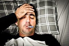 Drastisches Bild eines kranken Mannes im Bett mit Fieber lizenzfreies stockfoto