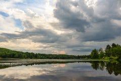 Drastisches cloudscape über dem Flusswasser mit Bäumen und Flecken von blauen Himmeln lizenzfreie stockfotografie