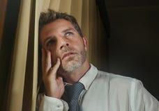 Drastisches Nachtlicht-Büroporträt des Geschäftsmannes das späte Lehnen gesorgt und frustriert auf dem Fenster bearbeitend durchd lizenzfreie stockfotografie