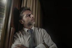 Drastisches Nachtlicht-Büroporträt des Geschäftsmannes gesorgt und frustriert auf dem Fenster spät sich lehnen bearbeitend durchd stockbild