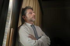 Drastisches Nachtlicht-Büroporträt des Geschäftsmannes gesorgt und frustriert auf dem Fenster spät sich lehnen bearbeitend durchd lizenzfreie stockfotos