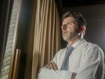 Drastisches Nachtlicht-Büroporträt des Geschäftsmannes gesorgt und frustriert auf dem Fenster spät sich lehnen bearbeitend durchd stockbilder