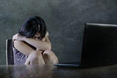 Drastisches Porträt des erschrockenen und betonten Jugendlichmädchens oder der jungen Frau mit Laptop-Computer der leidenden Cybe stockfotografie