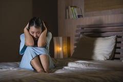 Drastisches Porträt des jungen schönen und traurigen asiatischen koreanischen Frauenschreiens hoffnungslos auf dem Bett wach an d stockbild