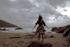 Drastisches Porträt langhaariger Dame in der Blumengesellschaftskleidung auf einem stürmischen Strand lizenzfreies stockbild