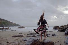 Drastisches Porträt langhaariger Dame in der Blumengesellschaftskleidung auf einem stürmischen Strand stockbilder