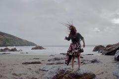 Drastisches Porträt langhaariger Dame in der Blumengesellschaftskleidung auf einem stürmischen Strand lizenzfreies stockfoto