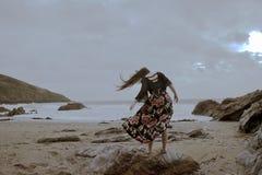 Drastisches Porträt langhaariger Dame in der Blumengesellschaftskleidung auf einem stürmischen Strand lizenzfreie stockbilder