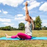 Draußen ausdehnen und meditierend, Trainieren der jungen Frau Stockfotos