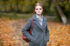Draußen bilden Porträt der schönen Rothaarigefrau mit herrlichem roten ledernen Rucksack schlendernd in Forest Park in Herbst war Stockfotos