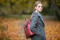 Draußen bilden Porträt der schönen Rothaarigefrau mit herrlichem roten ledernen Rucksack schlendernd in Forest Park in Herbst war Lizenzfreie Stockbilder