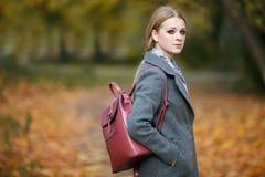 Draußen bilden Porträt der schönen Rothaarigefrau mit herrlichem roten ledernen Rucksack schlendernd in Forest Park in Herbst war Lizenzfreie Stockfotografie