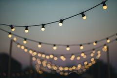 Draußen Heiratsdekoration mit Glühlampen bei Sonnenuntergang Lizenzfreies Stockbild