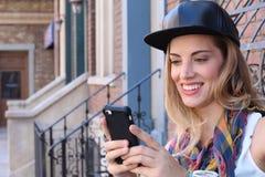 Draußen lächeln recht blonde Mädchenversenden von sms-nachrichten auf städtischem Hintergrund Lizenzfreies Stockbild