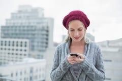 Draußen lächeln recht blonde Versenden von SMS-Nachrichten Stockfoto