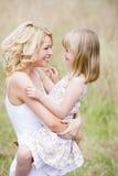 Draußen lächelnde Mutterholdingtochter stockfoto